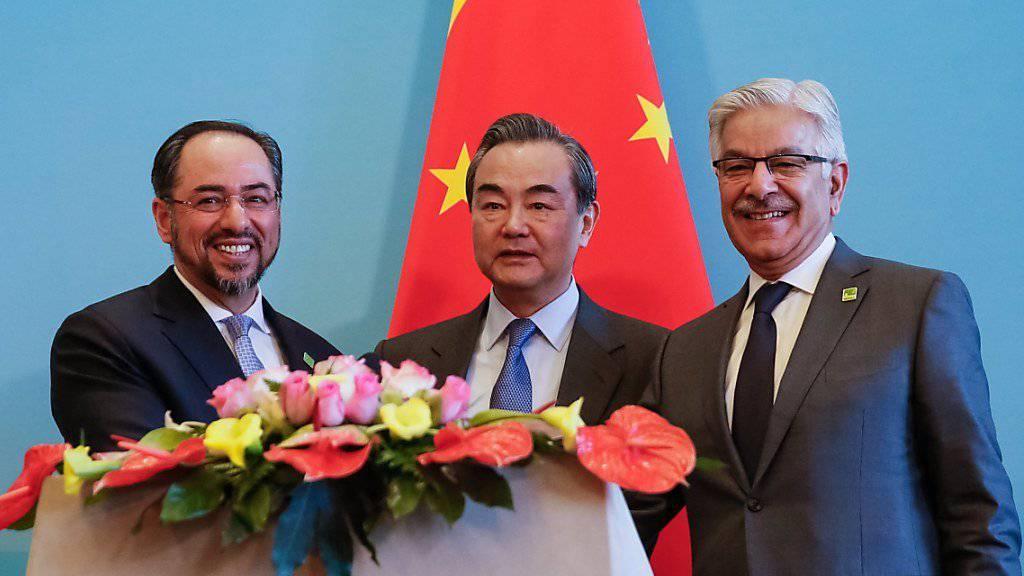 Chinas Aussenminister Wang Yi (M) mit seinen Kollegen aus Pakistan, Khawaja Muhammad Asif (r), und Salahuddin Rabbani aus Afghanistan