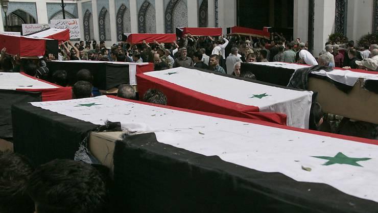Mit syrischen Flaggen umhüllte Särge in einem Vorort von Damaskus (Archiv)