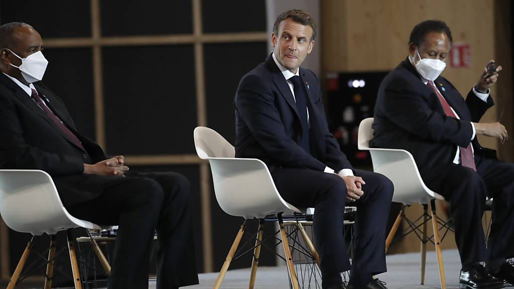 Emmanuel Macron (M), Präsident von Frankreich, Abdalla Hamdok (r), Premierminister des Sudan, und General Abdel Fattah Abdelrahman Burhan, Vorsitzender des sudanesischen Souveränitätsrats, nehmen an einer internationalen Konferenz über den Sudan teil. Eine internationale Konferenz zur Unterstützung des Sudans soll den Entschuldungsprozess des Landes einleiten. Foto: Christophe Ena/AP POOL/dpa