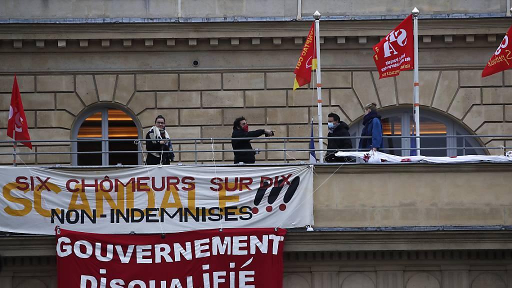 Arbeitslose französische Mitarbeiter der Kultur- und Tourismusbranche besetzen das  namhafte Odeon-Theater mit Bannern, auf denen zu lesen ist: «Die Regierung  ist disqualifiziert» und «Sechs von zehn arbeitslosen Arbeitern nicht entschädigt - Skandal!». Foto: Francois Mori/AP/dpa