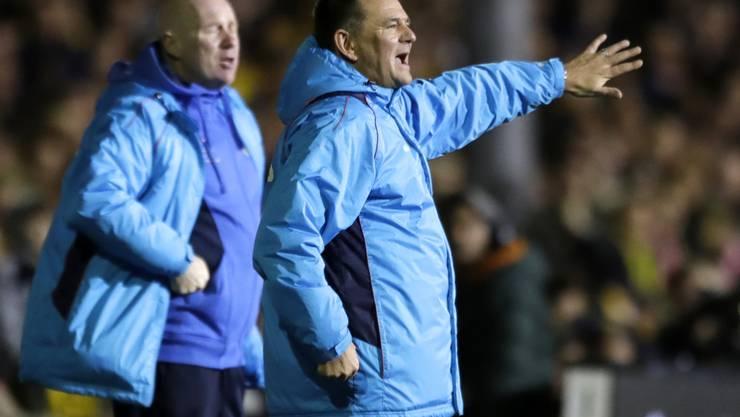 Sutton-Coach dirigiert sein Team und schaut nicht auf seinen essenden Ersatzhüter