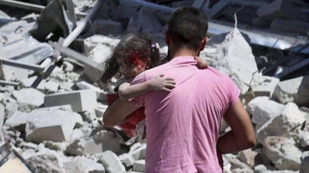 Durch Luftangriffe zerstört: In der Provinz Idlib sollen nun die Waffen schweigen. Ein Mann trägt in der Stadt Ariha ein verletztes Kind weg.