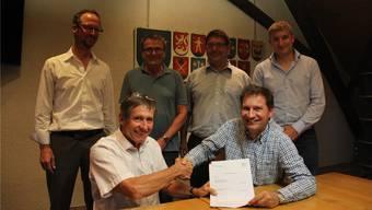 Der Konzessionsvertrag ist unterzeichnet: Gemeindeammann Roland König (links) und IBB-CEO Eugen Pfiffner geben sich die Hand. In der hinteren Reihe (von links): Richard Zickermann, Roland Meier, Philippe Ramuz und Benjamin Plüss.