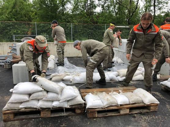 Die Zivilschützer bauen mit Sandsäcken einen Damm auf.