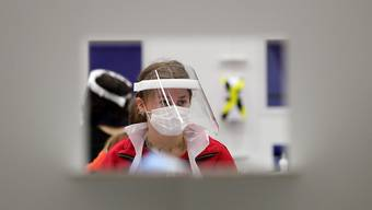 Eine Frau mit Mund-Nasen-Bedeckung und Gesichtsmaske wartet in einem Testzentrum der Universität Edinburgh. Foto: Andrew Milligan/PA Wire/dpa