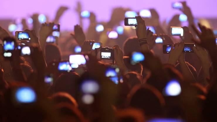 «Alle Hände in die Luft!», hiess es früher. Längst gehen die Handys in die Luft. Es sind Szenen, wie sie sich vor den grossen Bühnen abspielen. So wie auf diesem Bild an einem ausverkauften Rap-Konzert im Allgäu (D).