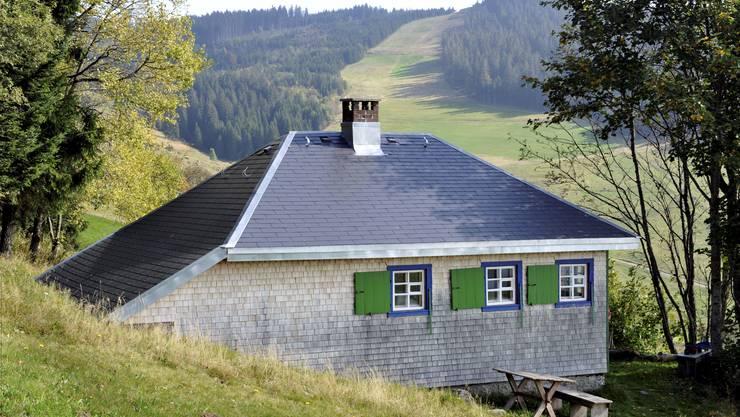 Heideggers berühmte Hütte in Todtnauberg (Schwarzwald). Vor dem Haus der Brunnen, mit einem Stern beim Ausguss.