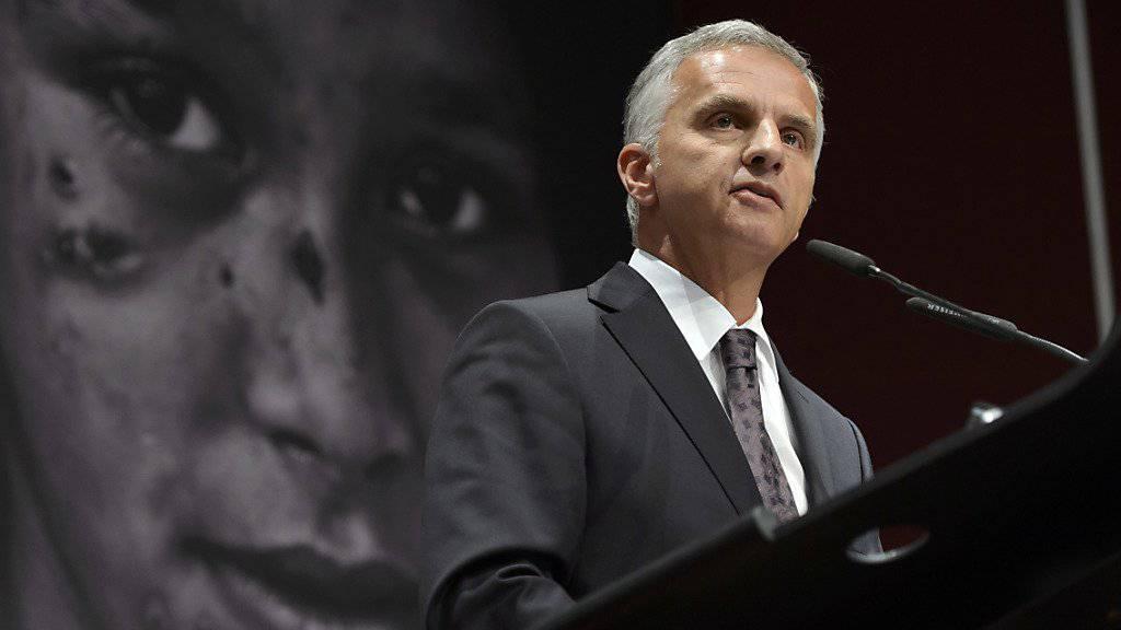 Bundesrat Didier Burkhalter fordert eine bessere Achtung des humanitären Völkerrechts. Im Hintergrund das Bild eines kriegsversehrtes Mädchen.