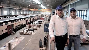 Projektleiter Christoph Tietz (links) und Werkleiter Thomas Widmann lassen in der riesigen Halle die Testzüge auf den neusten Stand bringen.