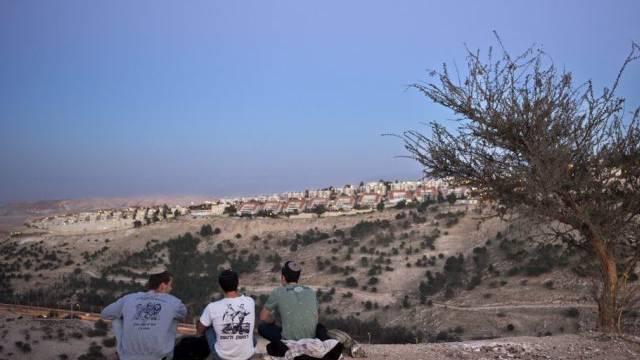 Drei Männer blicken auf eine israelische Siedlung im Westjordanland