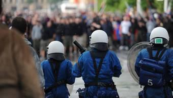 Hooligans und die Polizei stehen sich gegenüber. (Symbolbild)