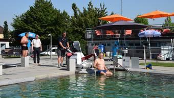 SP-Gemeinderat Roger Seger testet in der Badi Im Moos den von ihm angeregten neuen Pool-Lift. Badmeister Mihajlo Nikic bedient das mobile Gerät. Der zuständige Stadtrat Andreas Kriesi (GLP, 2.v.l.) und Abteilungsleiter Roger Gerber beobachten den Test. Alle vier ziehen danach eine positive Bilanz.