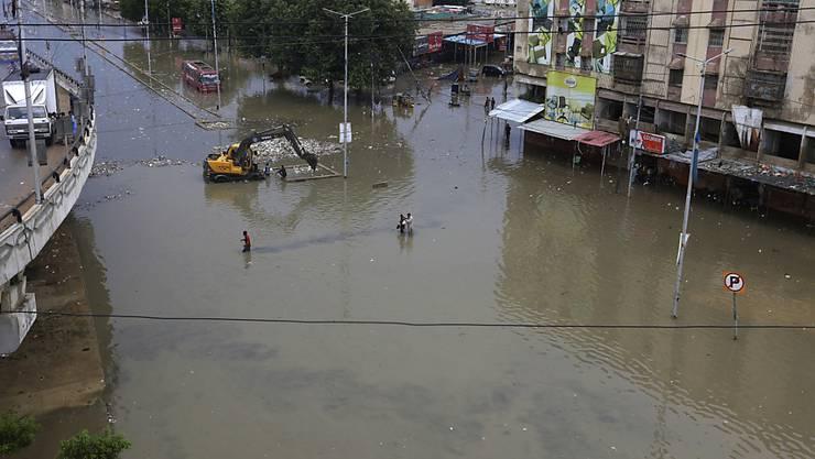 Menschen waten durch ein überschwemmtes Gebiet nach einem starken Regenfall in Karatschi. Foto: Fareed Khan/AP/dpa