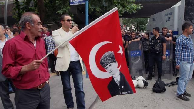 Ein Mann mit einer Fahne mit dem Bild von Staatsgründer Atatürk