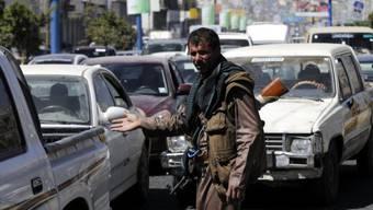 Ein Kämpfer der Huthi-Rebellen kontrolliert in Sanaa Autos