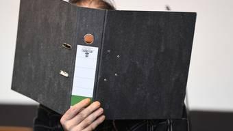 Der wegen Kindesmissbrauchs angeklagte Schweizer sitzt mit einen Aktenordner vor seinem Gesicht in einem Saal des Freiburger Landgerichts.