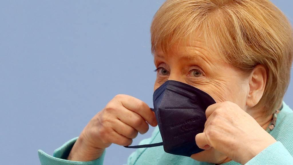 Bundeskanzlerin Angela Merkel (CDU) setzt sich ihre Maske auf. Foto: Wolfgang Kumm/dpa