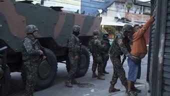 Soldaten durchsuchen während einer Razzia in einer Favela von Rio einen Einwohner.