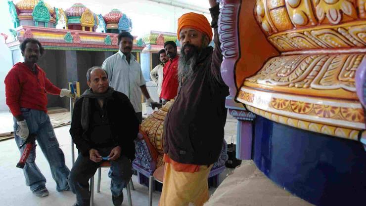 Tempelerbauer: Oberpriester Kurukkal (rechts) hat neben acht Handwerkern auch Götterfiguren, farbenfrohe Altäre und Schreine aus Südindien einfliegen lassen.