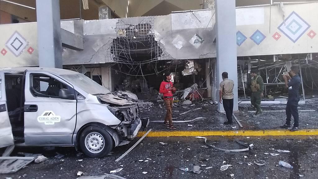 Menschen stehen in der Nähe eines beschädigten Gebäudeteils des Flughafens nach einer Explosion. Die Explosion traf das Flughafengebäude. Foto: Majid Saleh/AP/dpa