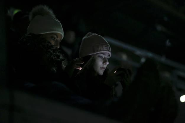 Fans vertreiben sich die Zeit während des Stromunterbruchs mit dem Smartphone.
