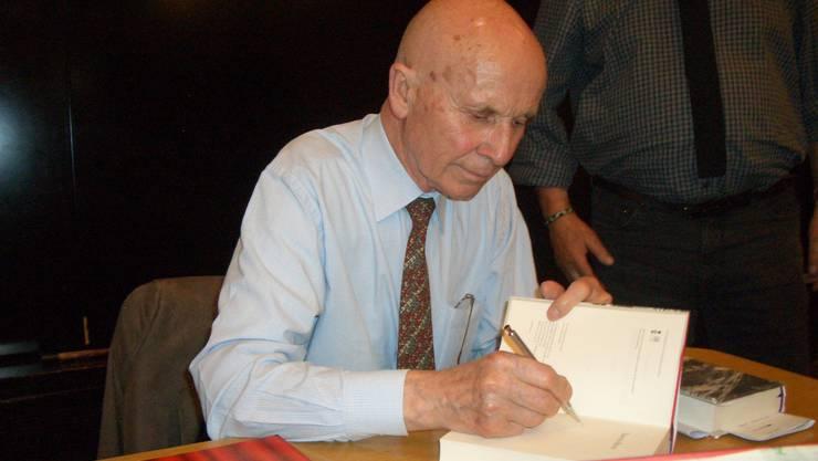 Schriftsteller Otto Zumoberhaus signiert seine Bücher