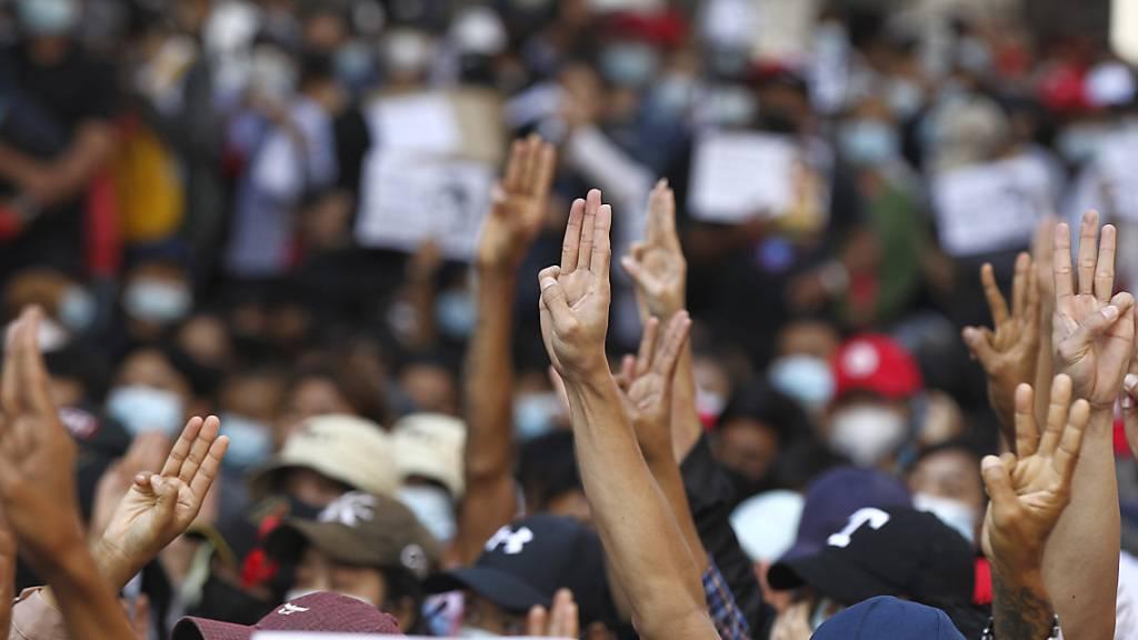 Demonstranten zeigen den Dreifingergruß während ihres Protestmarsches. Sie forderten die Freilassung der politischen Führung und die Rückkehr zur Demokratie. Die Proteste gegen die Putschisten in Myanmar breiten sich weiter aus. Foto: Uncredited/AP/dpa