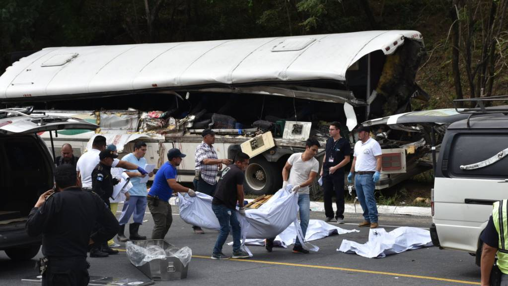 Schwerer Verkehrsunfall in Mittelamerika: Helfer tragen Leichen vom verunglückten Reisebus in Gualán in Guatemala weg.