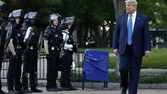 US-Präsident Donald Trump marschiert im Lafayette Park in der Nähe des Weissen Hauses in Washington neben Polizisten. (Archivbild)