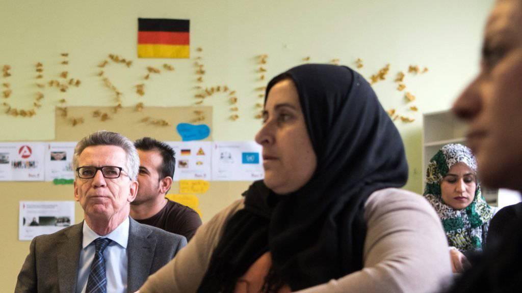 Deutschlands Innenminister Thomas de Maizière bei einer Orientierung mit muslimischen Asyl-Bewerberinnen
