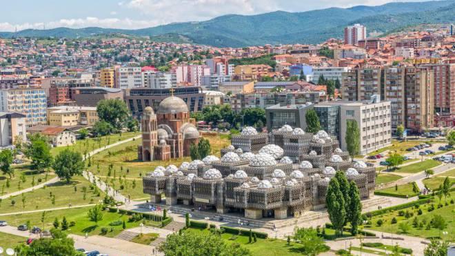 Architektonische Einzigartigkeiten: Die National- und Universitätsbibliothek in Pristina. Links die nie fertiggestellte orthodoxe Kathedrale «Christus der Erlöser». Foto: Shutterstock