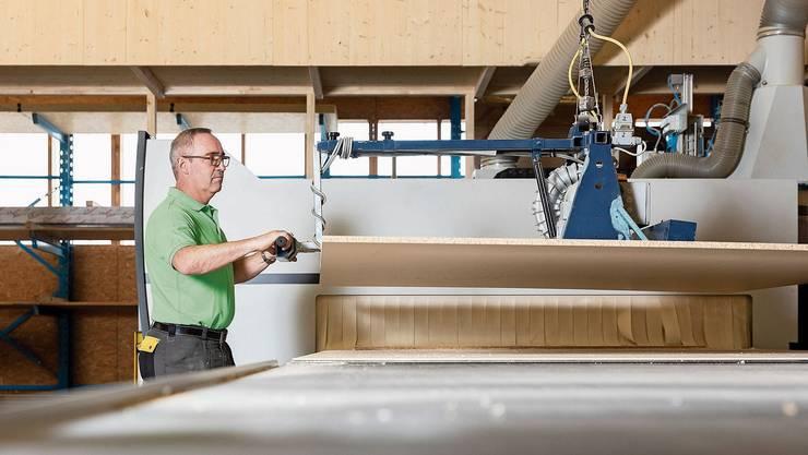 Christoph Zehnder hebt eine Platte auf die Maschine, wo danach die Bauteile des Schranks ausgeschnitten werden.