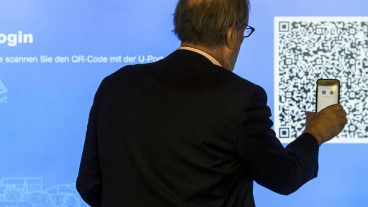 Der Zuger Stadtpräsident Dolfi Müller (SP) registriert sich auf der App, um mit seinem Handy an der ersten blockchain-basierten Abstimmung teilnehmen zu können. Die Stadt Zug will mit diesem E-Voting-System eine Vorreiterrolle in der Schweiz übernehmen.