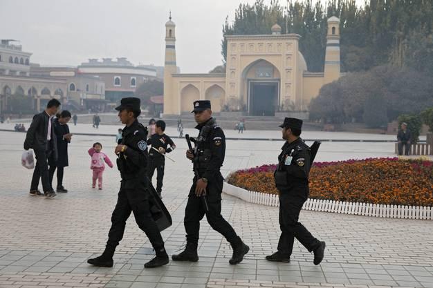 Chinesische Sicherheitskräfte patrouillieren vor einer Moschee in der von der muslimischen Minderheit der Uiguren bewohnten Stadt Kashgar.