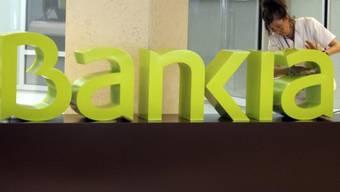 Eine Frau putzt das Bankia-Logo in Valencia (Archiv)