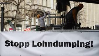 """Ein Banner mit dem Schriftzug """"Stopp Lohndumping"""" an der Fassade des Geschäftes des Modelabels """"Zara"""" an der Zürcher Bahnhofstrasse."""