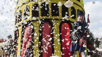 Ein Mann wirft Konfetti am Blumenkorso des Neuenburger Winzerfestes.