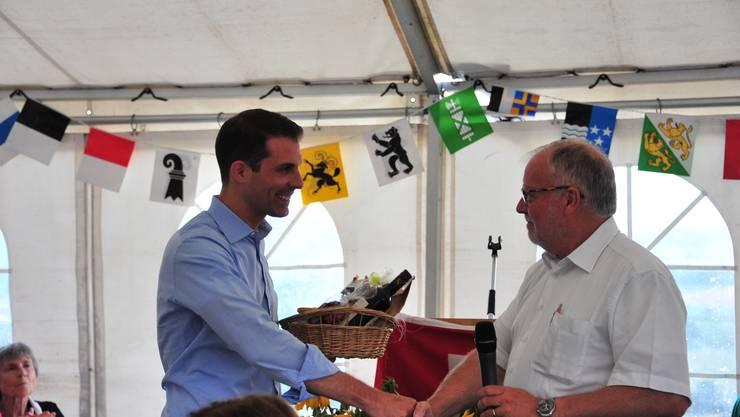 """""""Obwohl"""" er ein Badener ist, wurde Thierry Burkart in Freienwil herzlich willkommen geheissen. Ammann Robert Müller überreicht dem FDP-Politiker einen Korb mit Köstlichkeiten aus dem Dorf."""