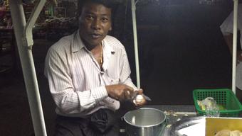 Messer-Skills in Myanmar: Ein Strassenkoch schneidet in seiner Hand hauchdünne Scheiben für eine Art burmesischen Zwiebelsalat.