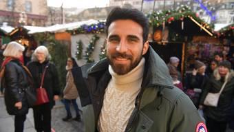 """""""Familiär feiern wir Weihnachten nicht, aber Geschenke gab es trotzdem immer"""", erzählt Eray Cömert am Basler Weihnachtsmarkt."""