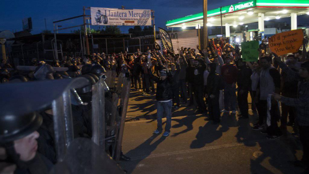 Demonstranten blockieren nahe von Tijuana eine Tankstelle und stehen Polizeikräften gegenüber