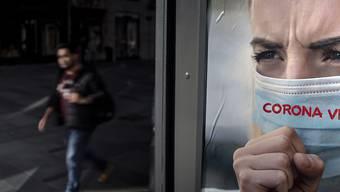 Ein Mann spaziert an einem Werbeplakat gegen das Coronavirus in Wien vorbei. (Archivbild)