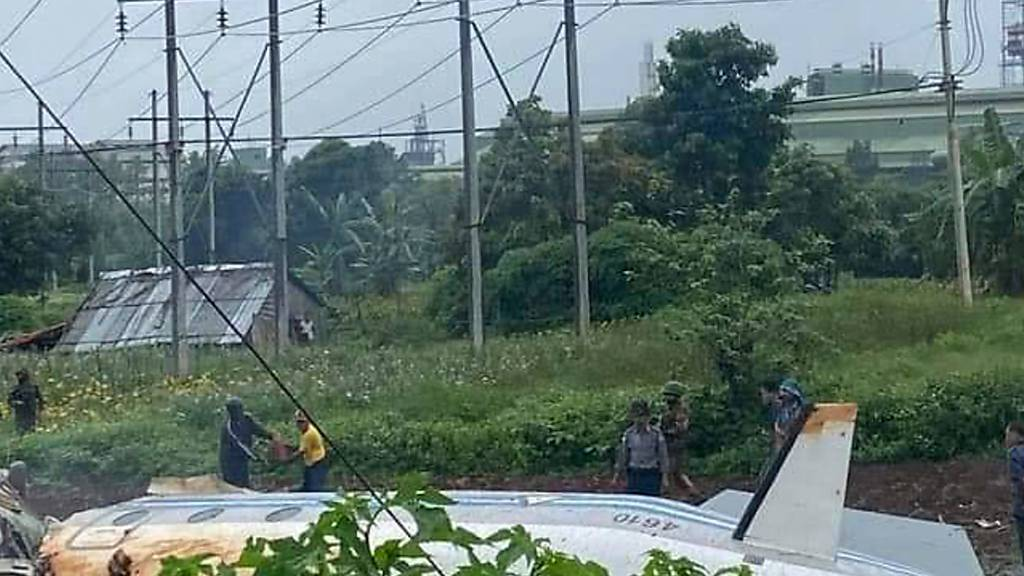 HANDOUT - Soldaten und Einheimische stehen neben dem Wrack einer Beechcraft 1900 der Myanmar Air Force, die  in Pyin Oo Lwin, Mandalay, Myanmar, abgestürzt ist. Zwölf der 14 Passagiere wurden getötet, wie die staatlichen Medien berichten. Foto: Uncredited/MYANMAR MINISTRY OF INFORMATION/AP/dpa - ACHTUNG: Nur zur redaktionellen Verwendung im Zusammenhang mit der aktuellen Berichterstattung und nur mit vollständiger Nennung des vorstehenden Credits