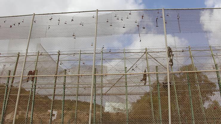ARCHIV - Nach einem Migranten-Ansturm hängen Kleiderfetzen am Grenzzaun von Melilla. Foto: Europapress/dpa