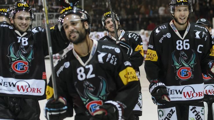 Fribourgs Marc-Antoine Pouliot (links), Michael Ngoy (Mitte) und Julien Sprunger (rechts) feiern nach dem Spiel den Sieg bei den Fans.