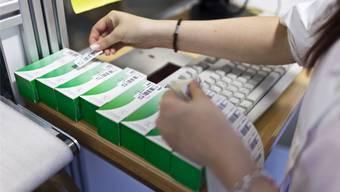 In einer Apotheke setzt eine Mitarbeiterin Strichcodes auf Medikamentenpackungen.