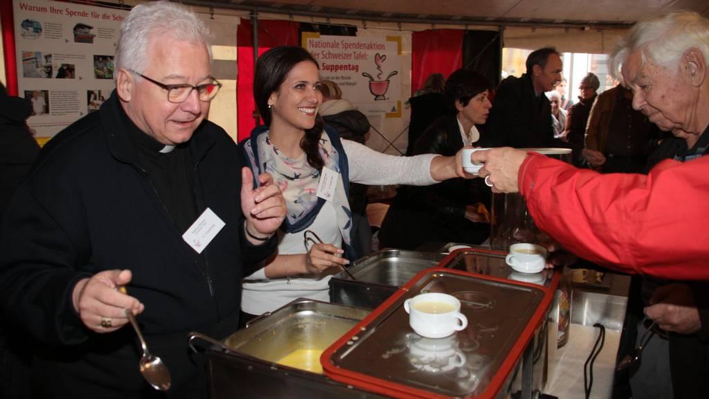 Bischof Markus Büchel und TVO-Moderatorin Claudia Marty schöpfen Linsensuppe für einen guten Zweck.