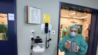 Ein Arzt transportiert während einer Nierentransplantation das Organ für die Implantation in den benachbarten Operationssaal. keystone