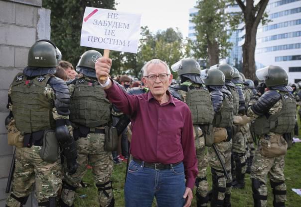 """Ein älterer Mann hält ein Plakat mit den Worten: """"Wir werden nicht vergessen. Wir werden nicht vergeben"""". Hinter ihm nehmen Soldaten Protestierende fest. (Bild: Keystone)"""