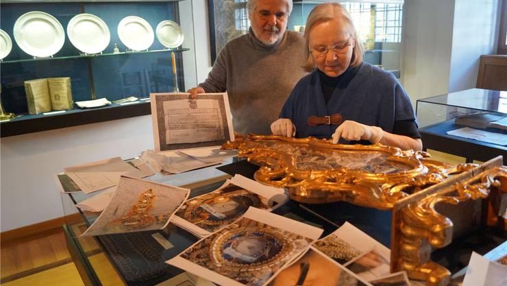 Inmitten von Bilddokumenten: Irene und Heinrich Briner begutachten ein golden glänzendes Behältnis mit Reliquien. sl